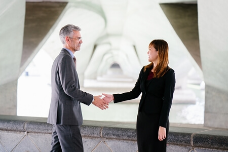 older-business-man-shaking-hands-with-young-professional-woman
